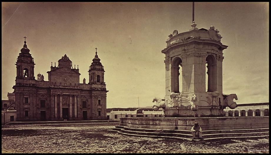 """La Plaza de Armas en 1875, con la Fuente de Carlos III en el centro, que fue utilizada irreflexivamente como paredón de fusilamiento en alguna ocasión . En la fotografía de Muybridge, la explanada de la plaza se encuentra libre de los """"cajones"""" y """"sombras"""" del mercado que la afeaban, según denuncias de José Milla, porque ya se había inaugurado el edificio del Mercado Central, justo detrás de la Catedral, en la Plazuela del Sagrario."""