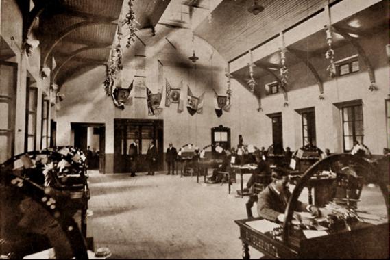 Interior de las oficinas centrales de Telégrafos. En la pared del fondo se puede observar al centro el retrato de Alexander Graham Bell (con las banderas de Estados Unidos y Guatemala a cada lado) y a su derecha el retrato de Marconi (con la bandera del reino de Italia y la bandera de Guatemala a cada lado). (Fotografía sin autor).