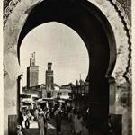 """Una de las puertas de Fez, desde las afueras de la ciudad. Sin fecha. """"Yo no sé cómo se llaman estas vías tan estrechas; pero supongo que, lo mismo que en España, llevan el nombre de alguna de sus menudas peculiaridades exteriores. La calle del Candil, la calle del Ciprés, la calle del Llamador, de cobre, la calle de la Puerta Grande, la calle de la Reja… Aunque, a decir verdad, esta última no la he visto todavía. Fuera de las puertas y de las ventanillas de mucharabié, que se observan en los paredones pardos, nada pone en comunicación el interior de los hogares con la vía pública. La vida verdadera, la vida íntima, comienza detrás de estas poternas…""""."""