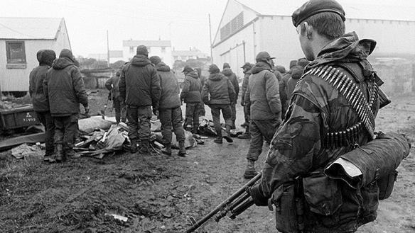 Soldados argentinos prisioneros, custodiados por un paracaidista británico en Port Stanley.