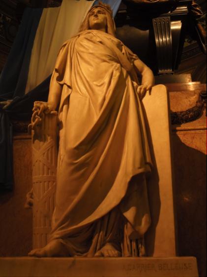 Detalle de una de las imponentes esculturas que escoltan el catafalco que guarda los restos del General San Martín. La alegoría de la libertad porta en su mano derecha las cadenas rotas de su cautiverio y se apoya en el haz romano, uno de los símbolos de la república. En su cabeza porta una corona de laurel, símbolo de la victoria. Su mano izquierda se apoya en lo que pareciera ser una tabla de la ley. A sus pies se puede leer la firma del A. Carrier Belleuse, quien lo ejecutó en 1880. Como dato curioso cabe mencionar que el mismo escultor realizó el monumento mortuorio y tumba del General Justo Rufino Barrios, levantado en el Cementerio General de ciudad de Guatemala. (Fotografía RFO).