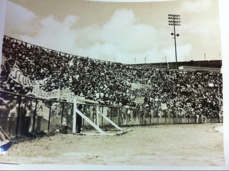 Imagen 4. Graderíos del Estadio Nacional atestados de manifestantes reunidos para conmemorar el séptimo aniversario de la Revolución de Octubre. En la esquina superior derecha pueden verse los vagones del ferrocarril, aparcados en los terrenos de FEGUA, dominando la vista del estadio.