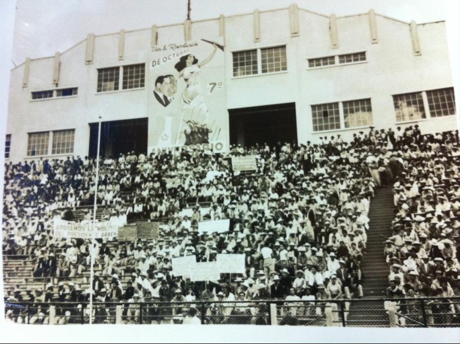"""Imagen 7. Puertas del Estadio Nacional, presididas por un enorme cartel conmemorativo del séptimo aniversario de la Revolución. En la esquina superior izquierda, los rostros de perfil de Jacobo Árbenz y Juan José Arévalo, imagen que se utilizó durante la campaña presidencial del primero, simbolizando la continuidad, bajo el lema """"Hoy Arévalo, Árbenz mañana"""". Al centro, la idealización de la revolución, encarnada en una mujer que enarbola un fusil. En la esquina inferior izquierda, una bandera de Guatemala ondea al viento. El vestido de la mujer sirve como fondo a un pelotón de hombres que marchan armados, se puede distinguir a un obrero, a un soldado y a un profesional, simbolizando la unión de clases que marchan con la revolución."""
