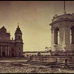 """Hermosa fotografía de Muybridge de la Plaza Mayor de la Nueva Guatemala de la Asunción, en el año de 1875. A propósito de ella escribió José Milla, en el Libro sin nombre (1870): """"Dominando la plaza mayor de esta ínclita ciudad desde un templete que lo abriga de la intemperie, está el caballo que montó el señor rey, no sé bien desde cuándo, hasta el año 1821, que apearon a S. M. sin ceremonia (…) El rey desapareció; era justo. ¿Cómo había de presidir un monarca a una plaza independiente, como la llama con gracia la lápida que está delante de la puerta principal del Ayuntamiento? Un caballo es otra cosa. Allí ha estado desde 1821 hasta 1870, con la cara hacia la catedral y las ancas hacia la antigua Audiencia, viendo correr el agua de la fuente, ocupación a que son dados todos los tristes…"""".[1]"""