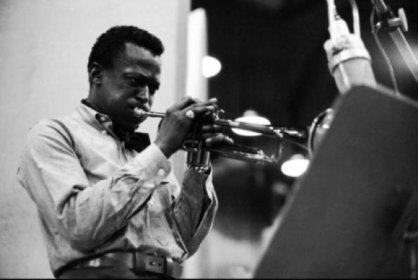 """Miles Davis, en una de las sesiones de grabación del Kind of Blue. De su importancia en el ámbito musical, apunta Joachim Berendt: """"…Más de treinta años de la historia del grupo en el jazz están marcados por los grupos de Miles Davis, señal de su intensa actividad, llevada más allá del ámbito de la trompeta y marcando la pauta para el desarrollo del jazz moderno."""""""