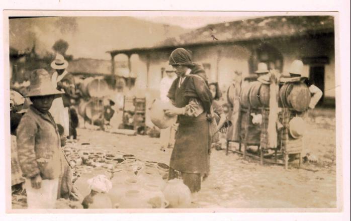 """Hermosa fotografía de un día de mercado en un poblado del altiplano. Atrás del hombre que sostiene una olla de barro pueden verse los cacaxtes, armazones de madera sobre las que los indígenas transportan los bienes que van a comerciar a la plaza. El proceso era definido por Tax, así: """"La producción de las tierras bajas, así como la de las altas, es transportada sobre la espalda por los indígenas, y negociada en los pueblos comerciales de las dos regiones…"""" (La fotografía corresponde a la década de 1920, nada habría cambiado a la estadía de Tax en Panajachel una década después)."""